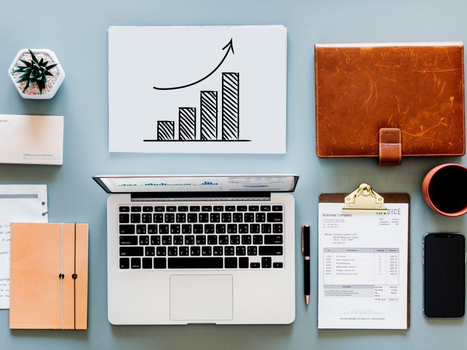 scrivania prdinata con pc, grafico, fattura, agenda e penna